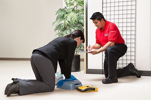 Cintas representative teaches how to perform CPR