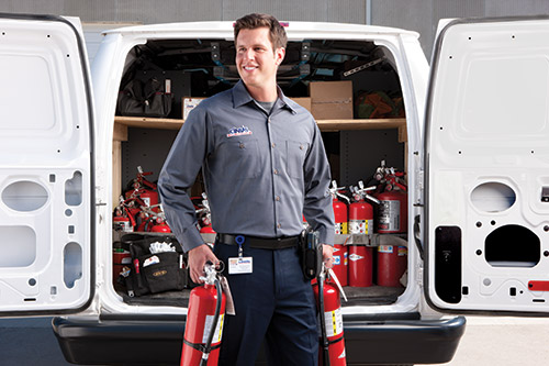 Cintas representative holding fire extinguishers in front of Cintas van with doors open and full of fire extinguishers