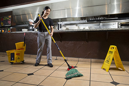 Restaurant employee using Bio-Based Floor Cleaner to clean a tiled floor