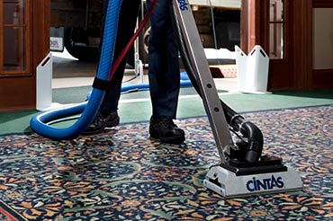 Cintas representative cleaning floral carpet with their cleaning machine