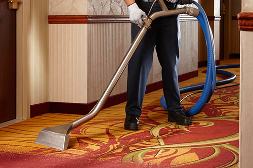 Cintas representative using steam cleaning machine to clean carpet