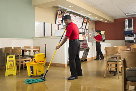 Employee cleaning tiled floor in a fast food restaurant using Floor Cleaner