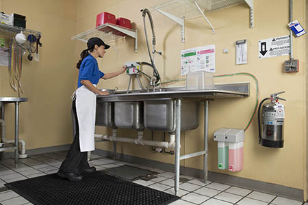 Employee filling a three-compartment sink with Foaming Degreaser