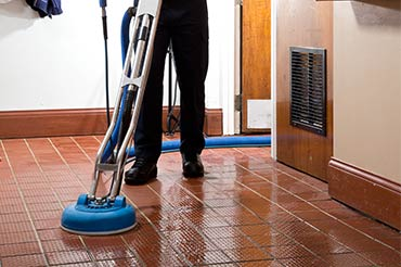 Cintas representative cleaning red tile with their cleaning machine