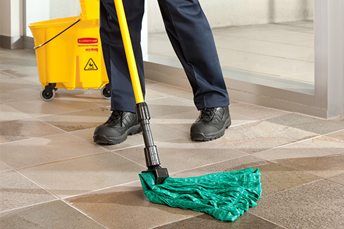 Employee mopping tiled floor