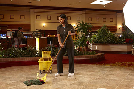 Employee using a Neutral Floor Cleaner to clean a hotel lobby's tiled floor