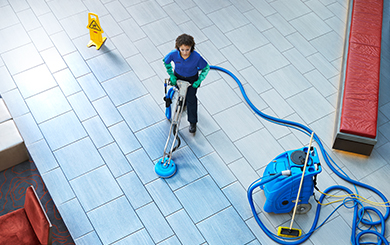 Cintas representative cleaning a tile floor