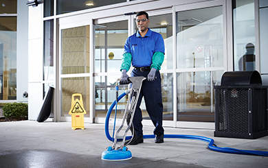 Cintas representative cleaning an outdoor concrete walkway