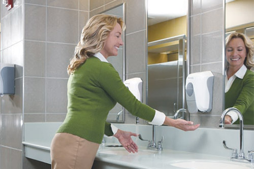 Happy customer washing hands in a clean bathroom