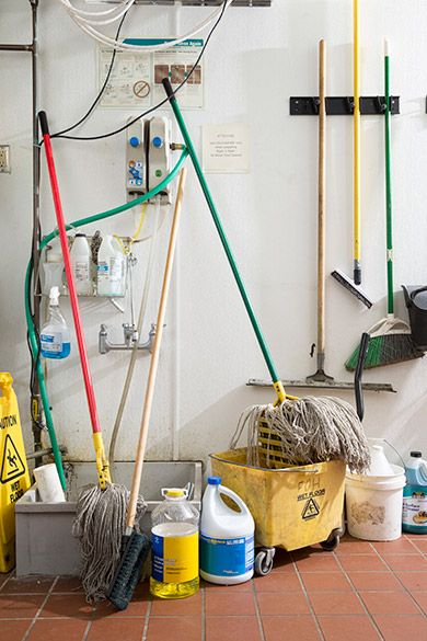 Dirty slop sink, mops, mop buckets, etc and empty chemicals before Cintas services