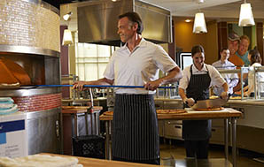 Pizza Chef wearing a ChefWorks® Chalk Stripe Apron putting a pizza in a wood-fired oven