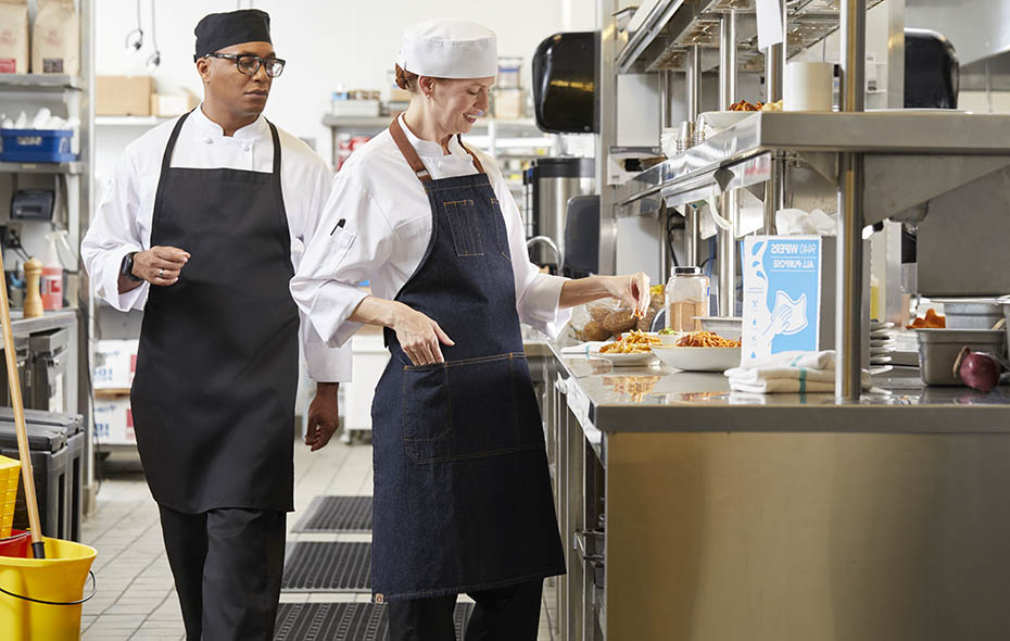 Female sous chef in a white chef beanie seasoning a dish as the head chef in a black chef beanie walks by and checks her work