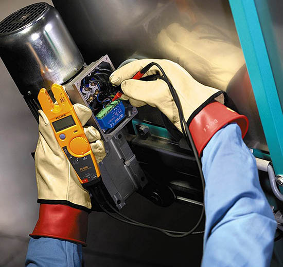 Electrician testing electronics in Arc Resistant Clothing and shock resistant gloves