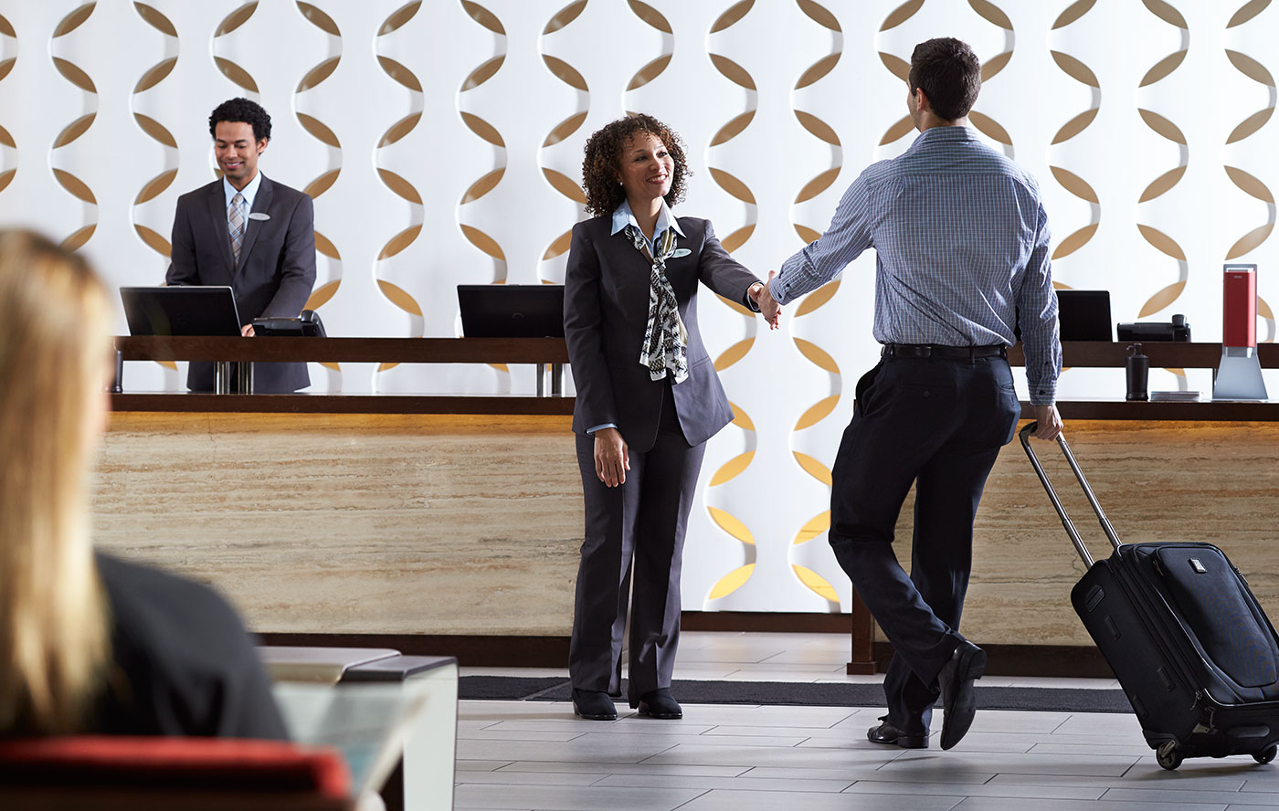 Woman in fitted pant-suit shaking hands with a hotel business customer