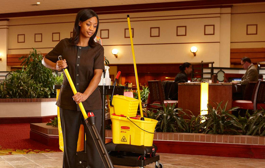 Woman in fitted brown shirt and pants mopping a hotel lobby