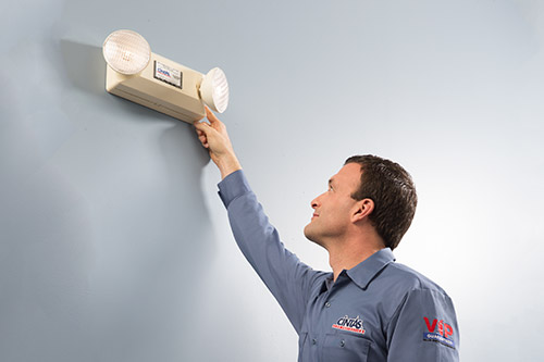 Cintas technician inspecting emergency light