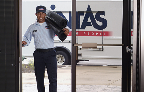 Cintas representative delivering new mats